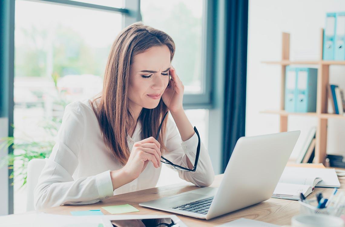 Una mujer frente a un ordenador con las gafas en la mano y tocándose la cabeza con señales de molestia