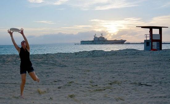 Foto de una chica jugando al frisbee al atardecer, en la playa, con un gran barco por detrás