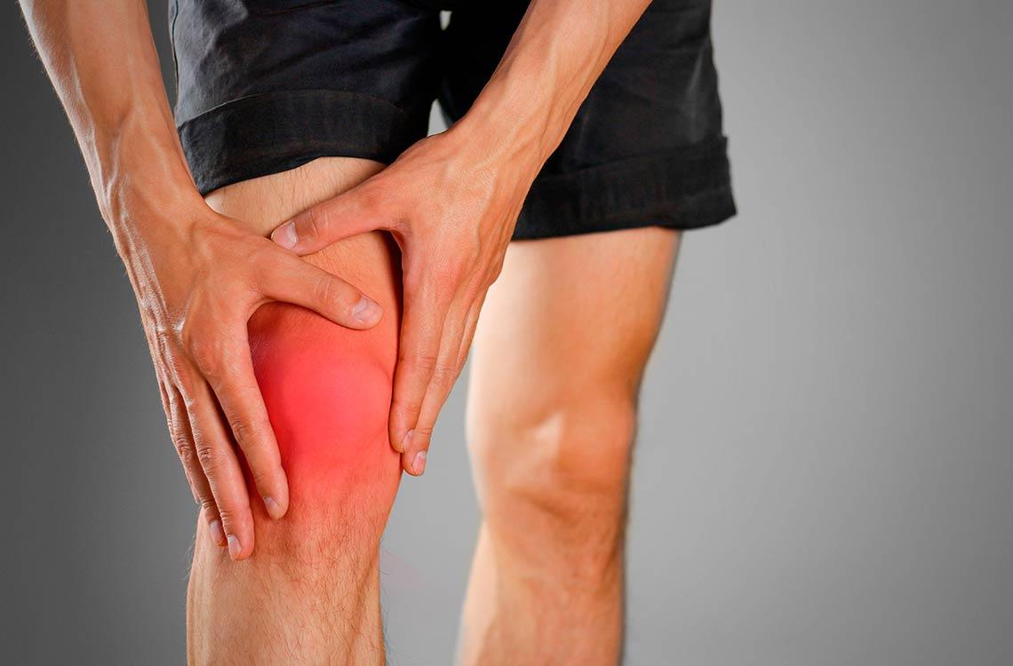 Un hombre se sujeta la rodilla marcada en color rojo, como síntoma de dolor o molestias