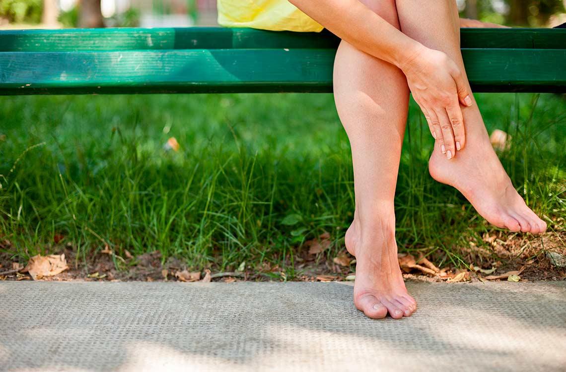 Una mujer se masajea el tobillo sentada en un banco