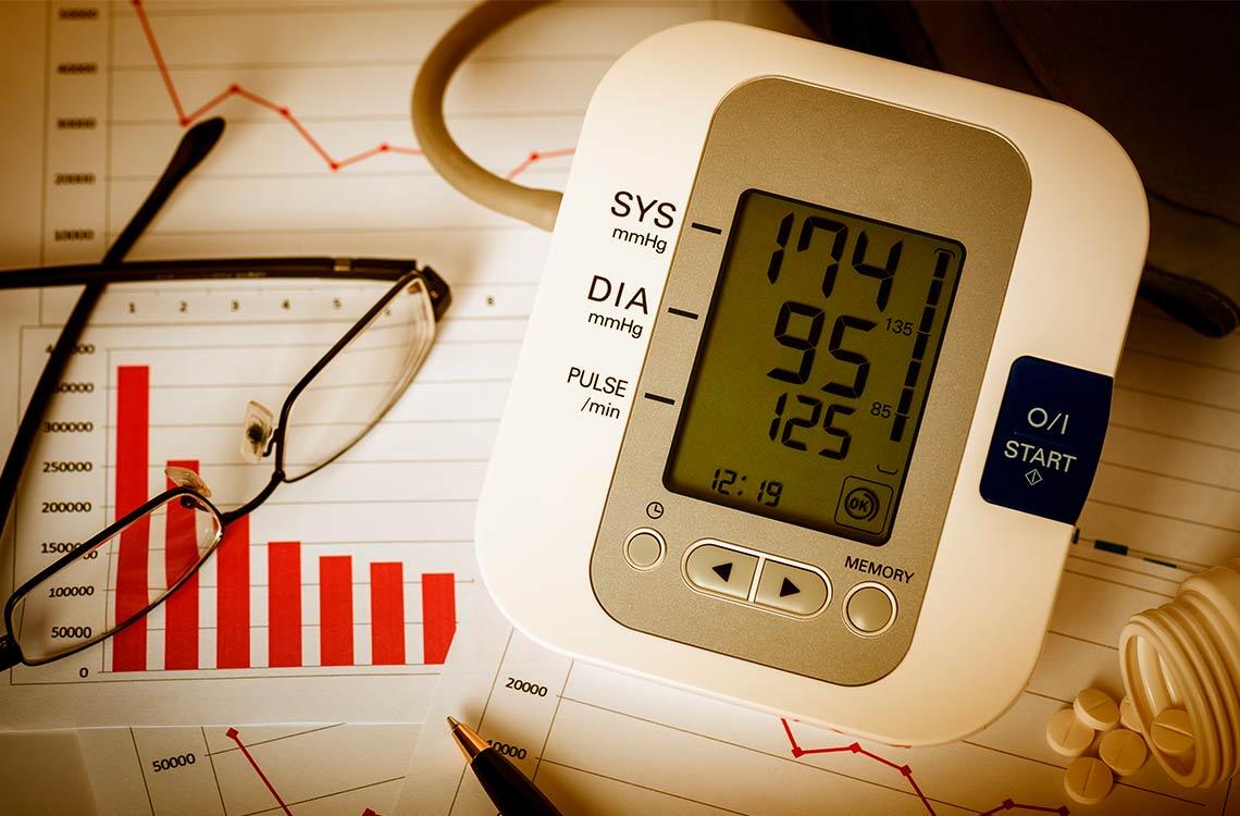 Aparato para controlar la tensión arterial sobre unos papeles y con gafas, pastillas y un boli alrededor